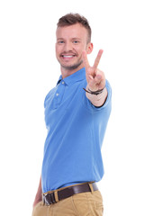 casual young man shows peace sign
