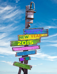 2015 happy new year on pastel colored wooden direction signs