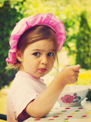 Vintage portrait of little girl eats with appetite