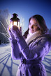 girl on winter snow with christmas lantern