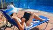 Woman sunbathing on deckchair with laptop