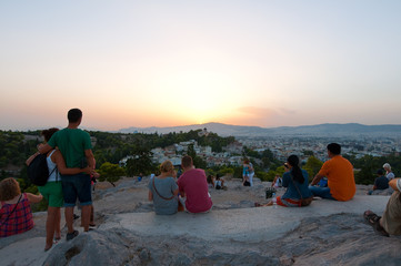 Tourists enjoy sunset from Areopagus hill. Athens, Greece.
