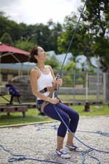 Asian Woman in belaying stance in outdoor rockclimb