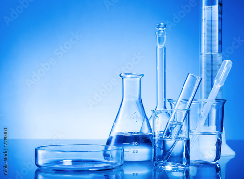 Laboratory equipment, glass flasks, pipettes on blue background