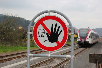 """Warnschild """"Zutritt verboten"""" vor einem herannahenden Zug"""