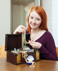 red-headed teenager girl looks jewelry