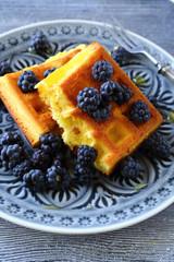 golden waffles with black blackberries