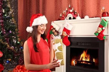 beautiful woman near the fireplace in winter house