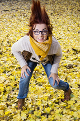 Young woman posing with hair in autumn leaves
