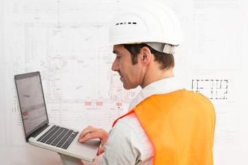 Architekt mit Notebook vor Grundriss