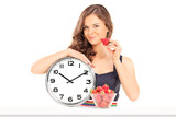 Beautiful woman holding a strawberry and a clock