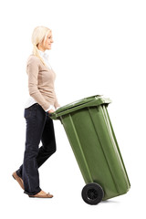 Cheerful young woman pushing a garbage can