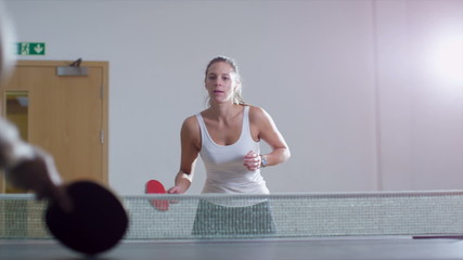 Young pretty woman playing table tennis