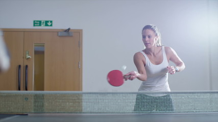 Slow motion clip of a pretty woman playing table tennis