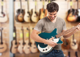 Man testing a guitar in a store
