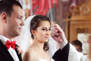 bride and groom in church front of priest