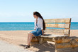 Young woman with long hair posing on a pier at the sea.