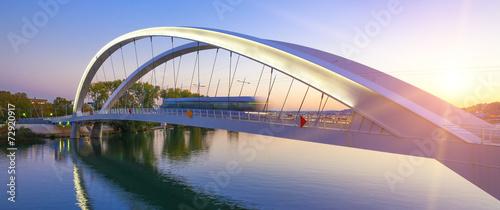 Tramway crossing bridge at sunset - 72920917