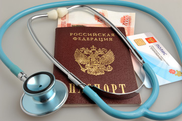 Stethoscope with passport, money and medical insurance policy on