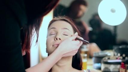woman applying make up to woman