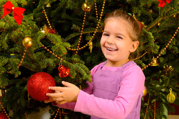 Adorable toddler girl holding decorative Christmas toy ball