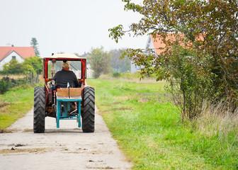 Landwirt fährt mit altem Traktor auf Güterweg