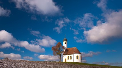 timelapse of moving clouds over single chapel in Bavaria