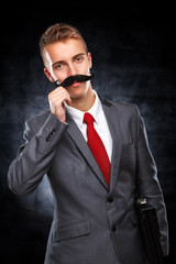 Young businessman with fake mustaches pretends to be older