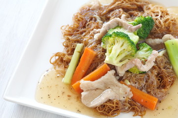 Fried noodle in gravy with pork and broccoli , carrot vegettable