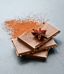 Pieces of chocolate with cocoa on balck background