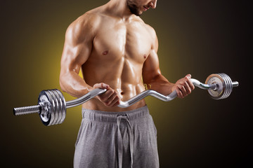 Fitness man lifting weights with curl bar against dark backgroun
