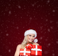 Beautiful girl in Christmas cap holds a set of gifts