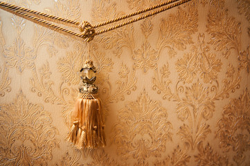 Beautiful golden tassel hanging on a rope on the background