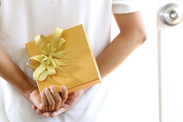 woman hiding gold gift box