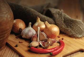 Onions, chili and garlic on a wooden table.