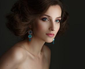 Portrait of beautiful young girl in earrings.