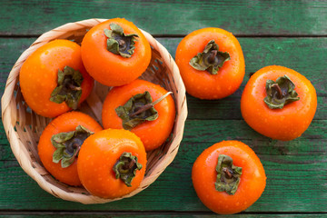 ripe persimmons in a wicker basket