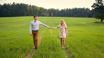 Loving Couple Holding Hands In Field