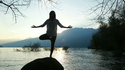 Woman practicing yoga near lake at sunset