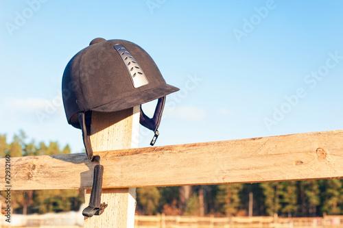Fotobehang Paardrijden Equestrian helmet forgotten hanging on the wooden fence.