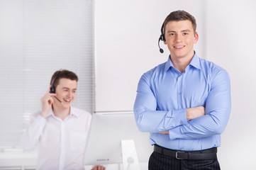 two young call center men talking by phone.