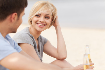 Man and woman relaxing on beach with beer