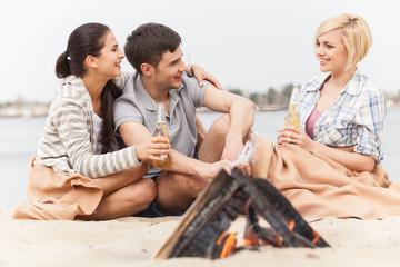 happy friends having fun around bonfire.