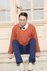 serious handsome man with glasses and sweater sitting on steps i