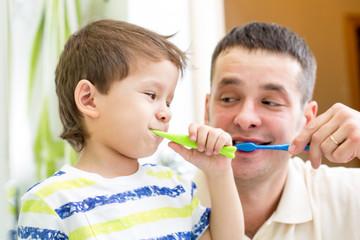 man and kid boy brushing teeth in bathroom