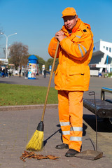 City janitor with broom tool during street sweeping