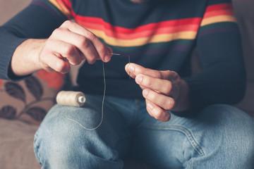 Man threading a needle