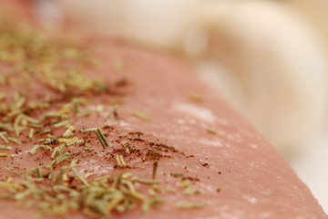 A close up of raw pork tenderloin with rosemary on top