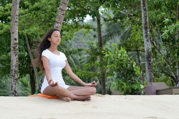 Healthy Woman Relaxing at the Beach with Yoga