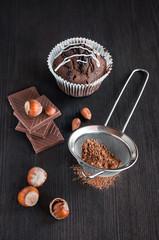 chocolate muffins with cocoa , chocolate bars and hazelnuts